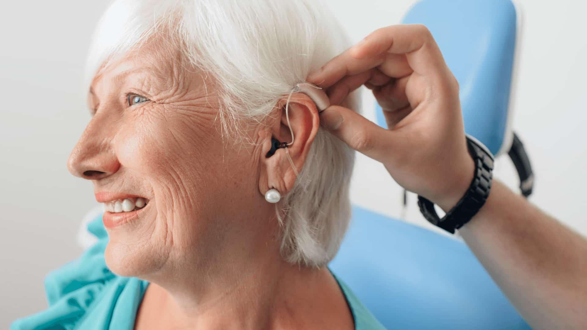 Colocando audífono mujer mayor